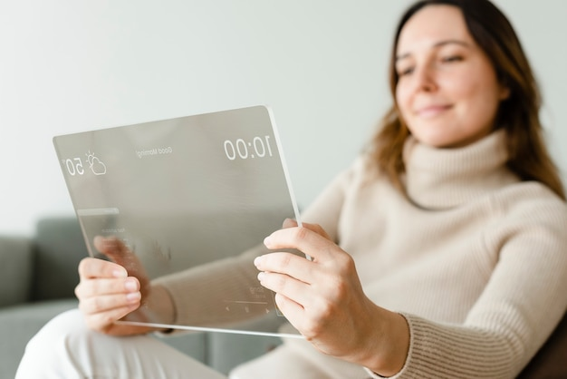 ソファの革新的な技術で透明なタブレットを使用している女性