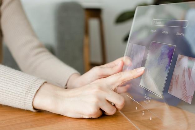 透明なタブレットを使用して音楽の革新的な技術を再生する女性