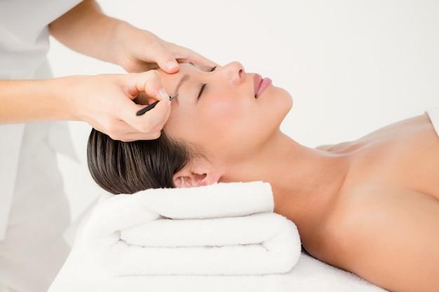 Woman using tweezers on patient eyebrow