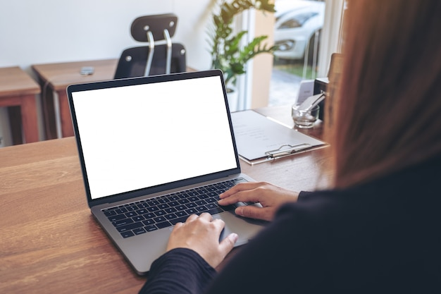 A woman using and typing on laptop with blank white desktop screen while sitting in office