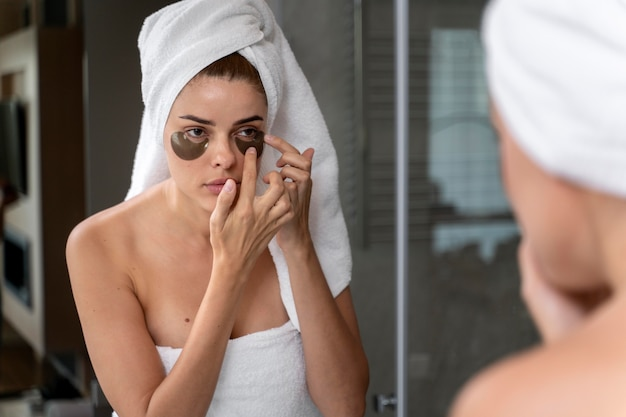 Woman using undereye masks in her bathroom