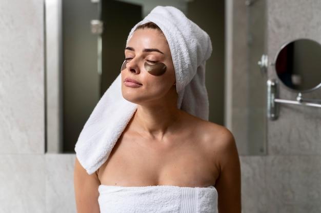 Женщина, использующая маски под глазами в ванной комнате