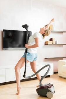 Woman using the vacuum as a microphone long shot