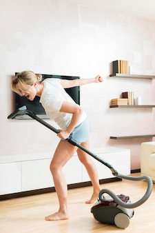 Woman using the vacuum cleaner as a microphone