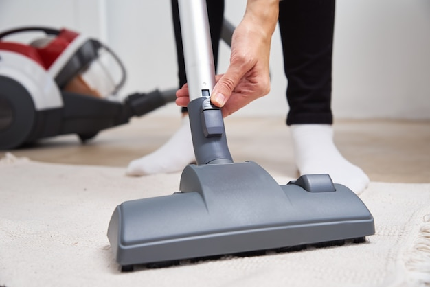 Женщина, использующая пылесос на полу