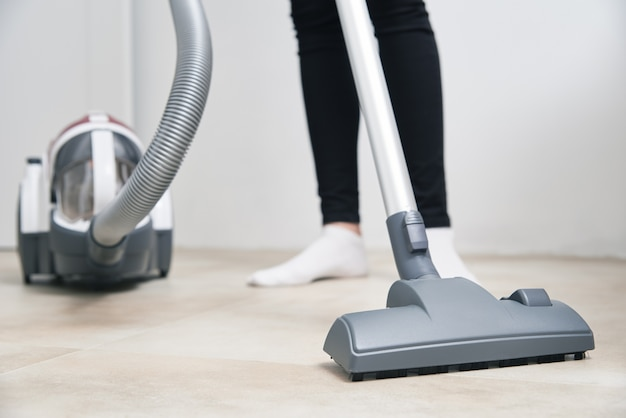 Woman using vacuum cleaner at floor