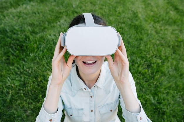 녹색 잔디에 외부 가상 현실 안경을 사용하는 여자