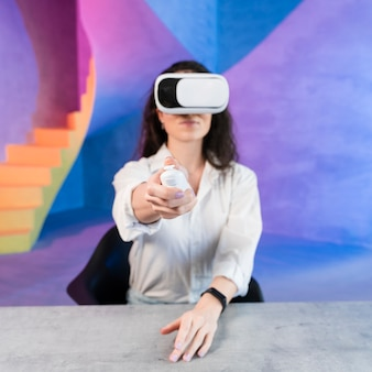 Woman using virtual reality headset and holding a remote