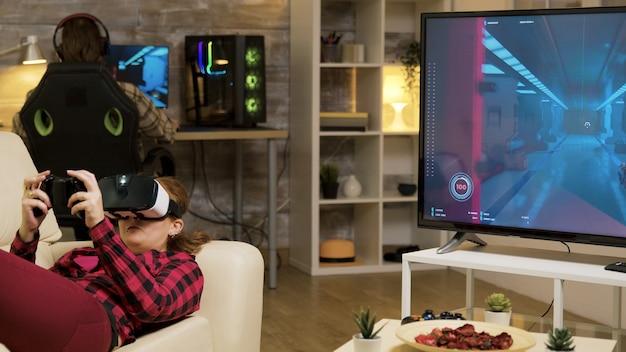 Женщина с помощью гарнитуры vr, чтобы играть в видеоигры и беспроводной контроллер, лежа на диване.