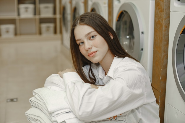 Woman using washing machine doing the laundry. young woman ready to wash clothes. interior, washing process concept