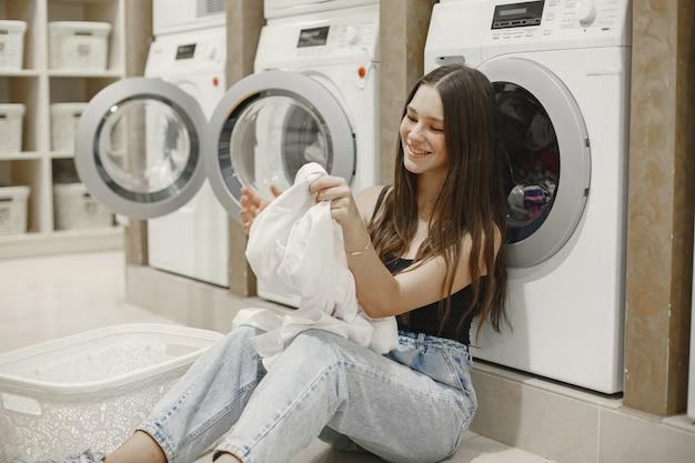 洗濯機を使って洗濯をしている女性。服を洗う準備ができている若い女性。インテリア、洗浄プロセスのコンセプト