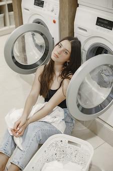 Женщина с помощью стиральной машины делает белье. молодая женщина готова мыть одежду. интерьер, концепция процесса стирки