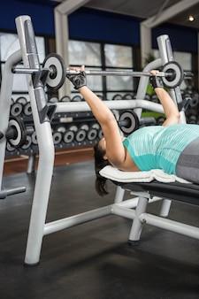 여자 팔 훈련 체육관에서 무게 기계를 사용 하여