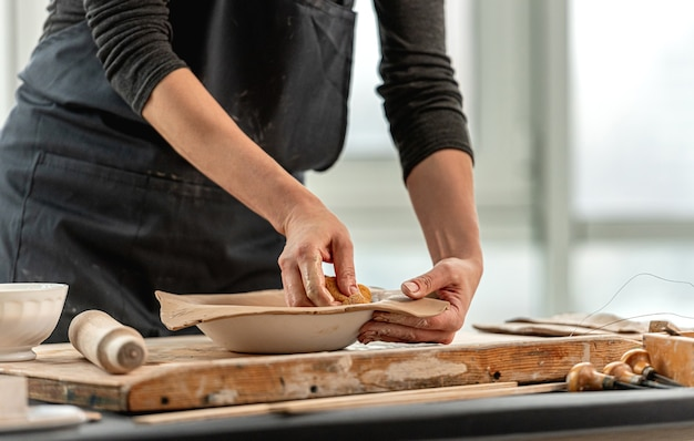 Woman using wet sponge for plate forming from clay at pottery workshop
