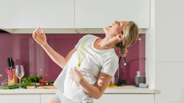 Woman using whisk as a microphone front view