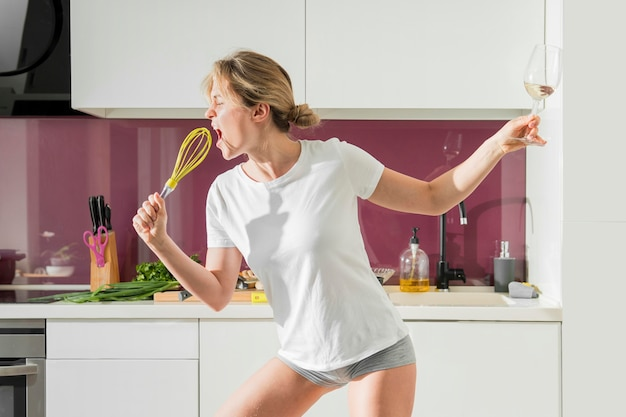 Woman using whisk as a microphone