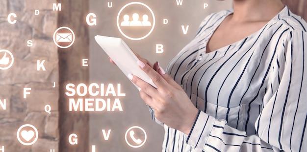 白いデジタルタブレットを使用している女性。ソーシャルメディア。通信網。技術。コミュニケーション
