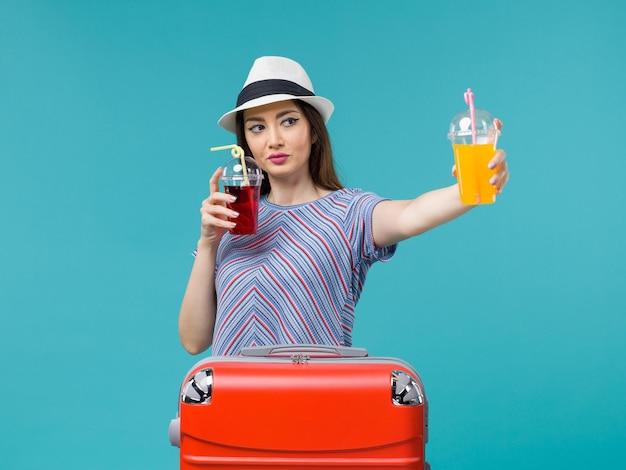 Donna in vacanza in possesso di bevande fresche su blue
