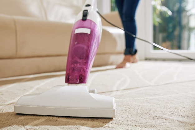 Woman vacuum cleaning carpet
