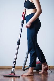 床を掃除機で掃除する女性