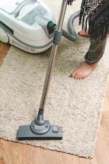 카펫을 진공 청소기로 청소하는 여자