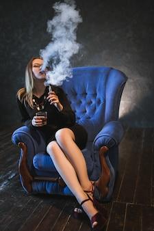 Женщина испаряет пары и пьет алкоголь, чтобы расслабиться. удовольствие от удовольствия и концепция охлаждения