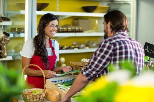 Женщина-продавец взаимодействует с мужчиной в продуктовом магазине
