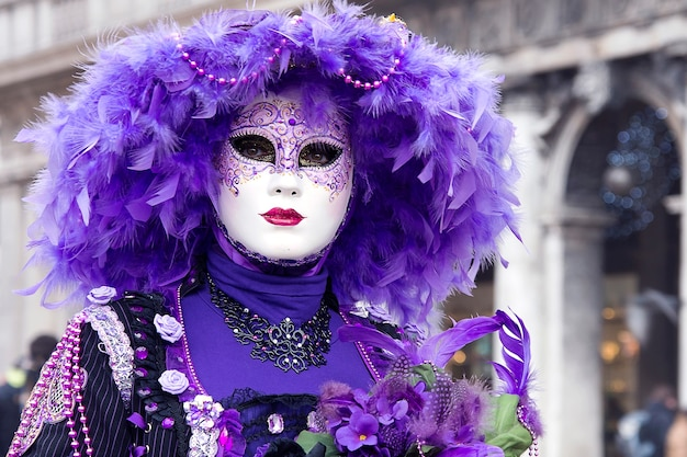 Woman in venetian carnival outfit in the city street. purple color. mardi gras. traditional carnival in venice