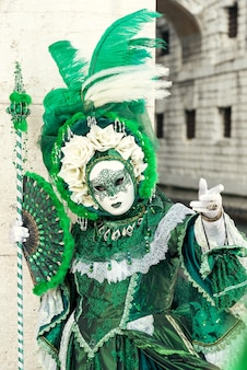 Woman in venetian carnival outfit holding fan and gesturind