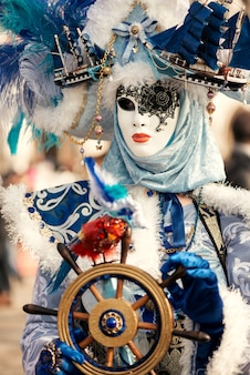 Woman in venetian carnival outfit holding steering wheel in hands marine concept