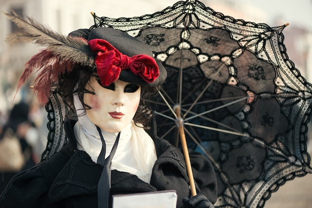 Woman in venetian carnival outfit with black umbrella