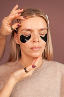 Woman vertical portrait with closed eyes and patches under the eyes with hydrogel