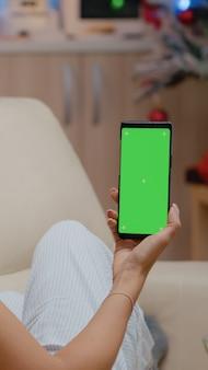 緑の画面でスマートフォンを垂直に保持している女性