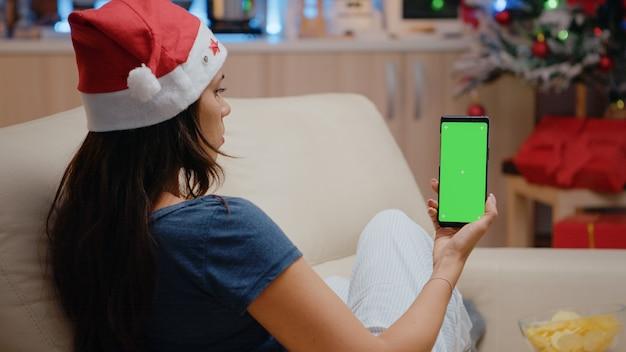 녹색 화면이 있는 스마트폰을 세로로 들고 있는 여성