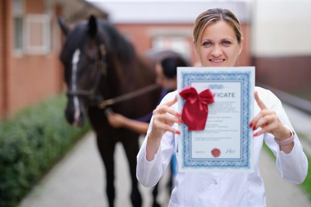 Ветеринар женщина держит сертификат обучения на фоне лошади