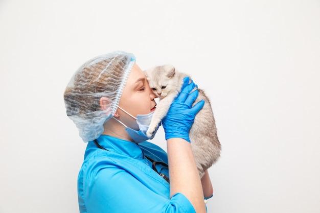 Ветеринар женщина в униформе со стетоскопом. у нее на руках белый британский котенок.