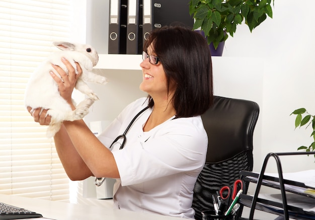 Женщина-ветеринар проверяет здоровье белого кролика