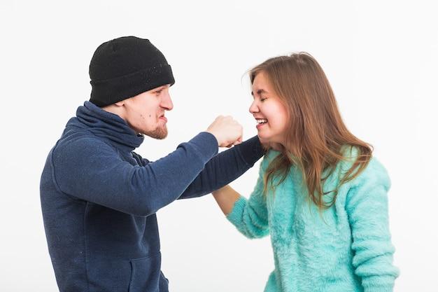 Женщина-жертва насилия и жестокого обращения. преступник избивает женщину на белой стене.