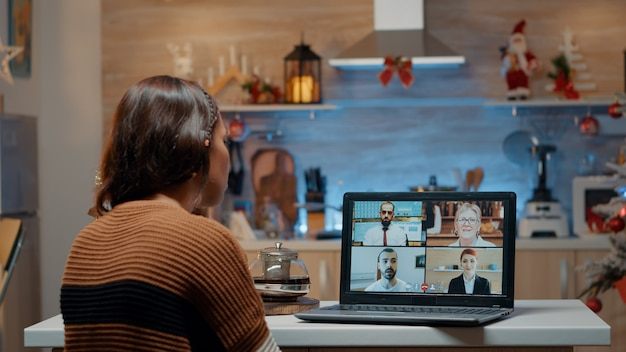 Woman on video call with workmates at home