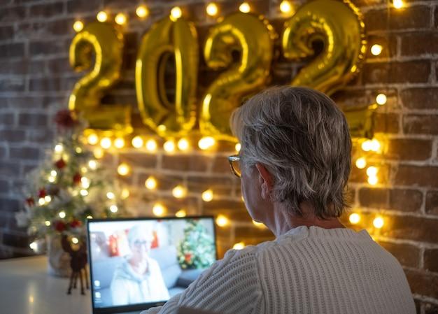 노트북에 여자 영상 통화입니다. 기쁜 성탄과 새해 복 많이 받으세요, 탁자 위의 작은 크리스마스 트리와 2022년 황금 풍선 숫자
