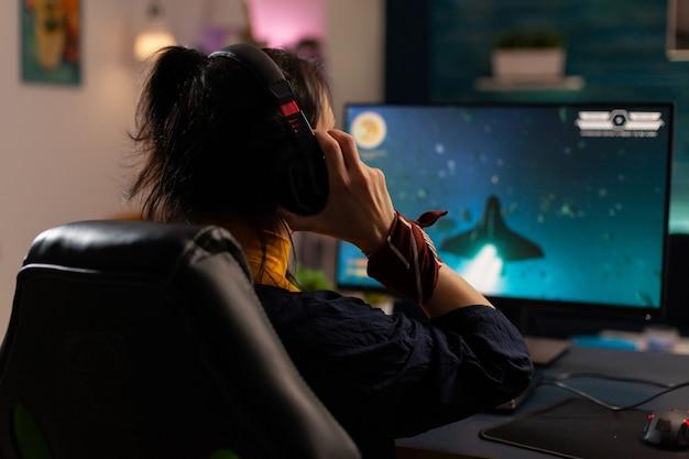 게임 홈 스튜디오에서 온라인 비디오 게임을 하는 강력한 컴퓨터를 사용하는 여성 비디오게이머. 전문 장비를 사용하여 게임 토너먼트를 수행하는 가상 스트리밍 사이버 uwearing 헤드폰.
