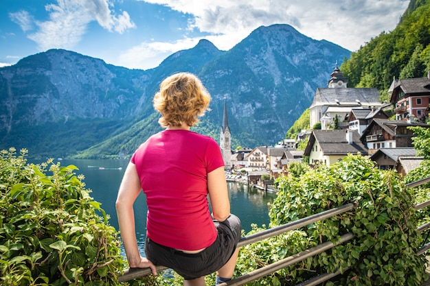 Woman on view point in austrian hallstat in summer, enjoying beautiful view of lake, city and mountains