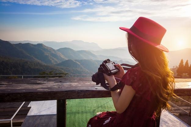 Женщина, просматривающая фотографии на камеру