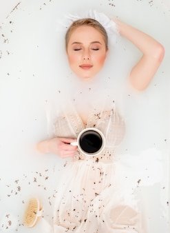 Woman in vintage clothes take a bath with lavender as in the days of the renaissance and drink a coffee