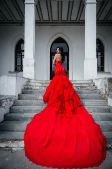 Женщина в винтажном красном платье старый замок красивая принцесса в соблазнительном платье элегантная кавказская женская сказка темная лестница