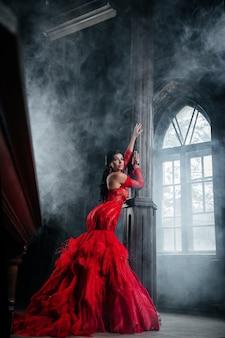 Женщина в винтажном красном платье старый замок красивая принцесса в соблазнительном платье элегантная кавказская женская сказка у большого окна с дымным туманом