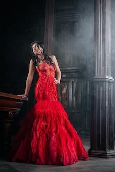 Женщина в винтажном красном платье старый замок красивая принцесса в соблазнительном платье элегантная кавказская женская сказка Premium Фотографии
