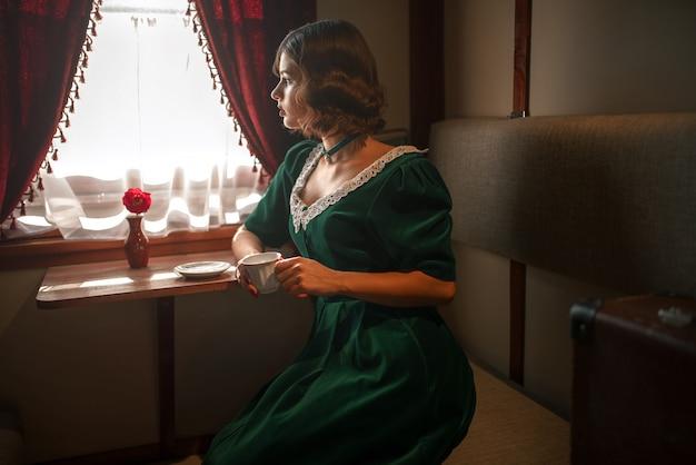 Woman in vintage train, rich compartment interior