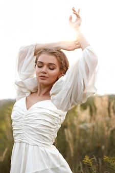 Woman in vintage white dress in the field at sunset