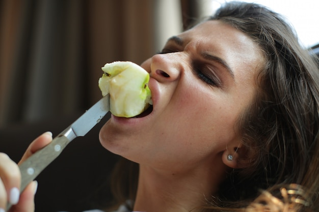 The woman violently bites an apple with a knife.